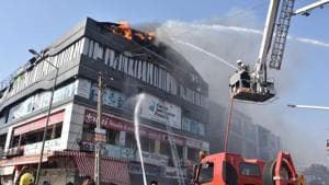 Firefighters fighting the blaze at Takshila complex in Surat in which 23 students died.(HT PHOTO)
