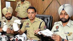 Police officials showing the recovered hand grenades and mobile phone at a press conference in Amritsar on Monday, June 3, 2019.(HT Photo)