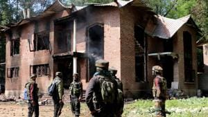 Army jawans stand guard outside a damaged house after a gun battle between militants and security forces at Panjran Pulwama district of south Kashmir on Friday. Four militants were killed in an encounter with security forces.(ANI photo)