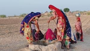 Women fetch water from a traditional well in a Barmer village.(HT)