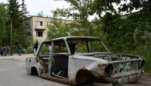 A picture taken on June 7, 2019, shows the wreckage of a car in the ghost city of Pripyat in the Chernobyl exclusion zone on June 7, 2019.(AFP)