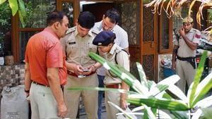 Police officials seen checking a mobile phone outside Shri Prakash Singh's house, at Sector 49, in Gurugram.(Yogendra Kumar/Hindustan Times)
