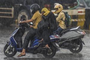 Bikers brave the rain at Chheda Nagar on Saturday.(Pratik Chorge/HT Photo)