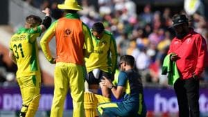 Australia's Usman Khawaja (C) receives medical attention during the 2019 Cricket World Cup group stage match between Australia and South Africa at Old Trafford in Manchester, northwest England, on July 6, 2019. (Photo by Paul ELLIS / AFP) / RESTRICTED TO EDITORIAL USE(AFP)