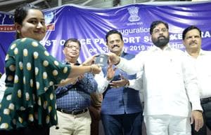 A resident receives her passport from Thane guardian minister Eknath Shinde after the inauguration of the new passport office at Vashi Post Office on Saturday.(Bachchan Kumar/HT)