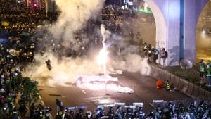 Thousands of masked pro-democracy demonstrators briefly occupied the road outside the office in the semi-autonomous city Sunday night and targeted the building with eggs, projectiles, laser lights and graffiti in a stark rebuke to Beijing's rule.(AP Photo)
