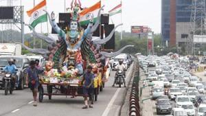 Kanwariyas pulling a Maha Kanwar decorated as a temple of Lord Shiva carrying holy water collected from the Ganga river at Delhi-Gurugram expressway, Sirhaul toll plaza, in Gurugram, on Monday, July 29, 2019.(Yogendra Kumar/HT PHOTO)