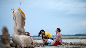 A family prays near the ruins of a headless Buddha statue, which has resurfaced in a dried-up dam due to drought, in Lopburi, Thailand.(REUTERS)