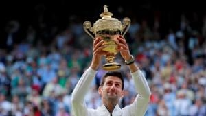 Serbia's Novak Djokovic poses with the trophy as he celebrates winning the final against Switzerland's Roger Federer.(REUTERS)