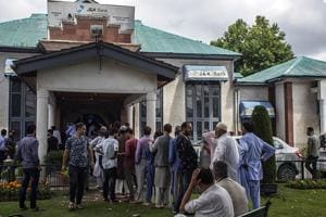 People wait in a queue outside J&K Bank in Srinagar on Tuesday.(ANI Photo)