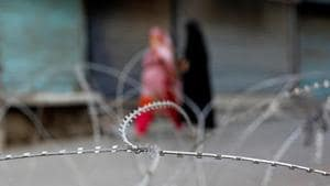 Kashmiri women walk past concertina wire laid across a road during restrictions after the scrapping of the special constitutional status for Kashmir by the Indian government in Srinagar.(REUTERS)