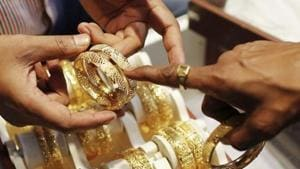 An employee shows gold bangles to a customer at a jewellery showroom. On Monday, gold prices stood at Rs 38,449 per 10 gram, while silver was at at Rs 46,880 per kilogram.(Reuters)