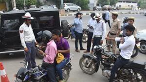 Traffic police personnel issue challans to those violating traffic rules at Maharana Pratap Chowk, in Gurugram.(Yogesh Kumar/Hindustan Times)