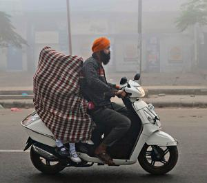 UP sheet street: Going to school in smog caused by crop burning.(AFP)