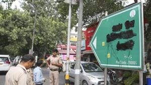 Police personnel stand beside the blackened signboard for Babar Road in New Delhi on Saturday. Right-wing outfit Hindu Sena blackened the signage in Bengali market demanding that it be renamed.(PTI PHOTO.)