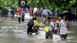 People wade through a flooded street aftert heavy rainfall in Patna on Saturday.(ANI PHOTO.)