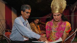 BP Gaur helping his son Deepak Gaur to prepare for the role of Ram in Sector 22, Chandigarh, on September 1.(RAVI KUMAR/HT)