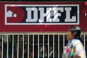 A woman walks past a signboard of Dewan Housing Finance Corporation Ltd (DHFL) in Mumbai. The premises of the corporation were raided on Saturday over alleged links with Iqbal Mirchi, an aide of underworld don Dawood Ibrahim.(Reuters file photo)