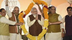 Prime Minister Narendra Modi is garlanded as he arrives to addresses his supporters after Haryana and Maharashtra election results were declared at party headquarters in New Delhi on Thursday, October 24.(Burhaan Kinu/HT PHOTO)