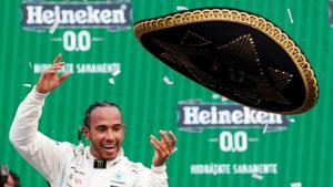 Mercedes' Lewis Hamilton celebrates winning the race on the podium throwing a sombrero(REUTERS)
