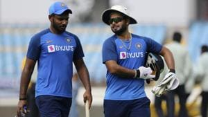 Indian players Rishabh Pant, right and Sanju Samson return after a practice session.(AP)