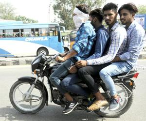 MULTIPLE VIOLATIONS, FATAL THRILLS: Four youth riding a motorbike without wearing helmets on Patiala-Sangrur road on Monday.(HT PHOTO)