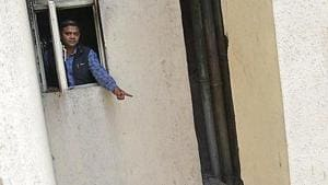 A man points to the beam on to which Rahul Singh had jumped to save himself from the fire on Tuesday morning.(Sakib Ali/ht photo)