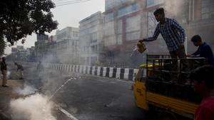 Police clear road blocks as a man tries to douse a fire set by protesters in Guwahati, Assam, on Thursday.(AP Photo)