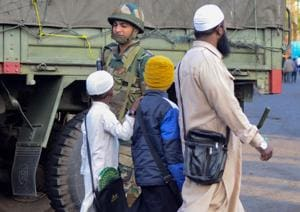 A man along with children walk past him a security personnel during relaxation of curfew, in Dibrugarh, Friday, Dec. 13, 2019. Curfew was relaxed for a few hours on Saturday and Sunday as well.(PTI)