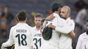 Australian bowlers Mitchell Starc and Nathan Lyon hug after winning their cricket test against New Zealand in Perth.(AP)
