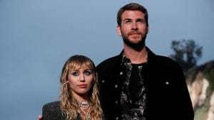 Miley Cyrus and Liam Hemsworth look on at the Saint Laurent Men's Spring/Summer 2020 fashion show at Paradise Cove beach in Malibu, California.(REUTERS)