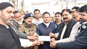 Muslims in Bulandshahr handing over a Demand Draft to compensate the damages to property in anti-CAA protests.(HT Photo)
