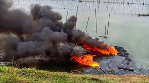 Plumes of smoke rise over a small stream of the Burhi Dihing River.(PTI)