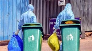 Medical staff, wearing protective suits, hold medical waste as they leave the special isolation ward set up to provide treatment to coronavirus patients, Kochi Medical College, Kerala, February 4, 2020(PTI)