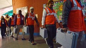 Polling officials seen carrying EVMs.(Sanchit Khanna/HT PHOTO)