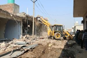 The district administration demolished 12 of the 83 illegal structures falling within the 100-metre radius of the boundary wall of the air force station in Bhabat village of Zirakpur on Thursday.(Sushil Prajapati/HT)