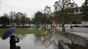 Tokyo: A woman takes pictures of the Olympic rings near the New National Stadium in Tokyo.(AP)