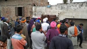 Residents of Moole Chak village of Amritsar gather outside the house whose roof collapsed after rain on Friday morning.(Sameer Sehgal/HT)