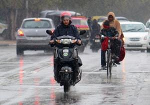 Commuters caught in rain in Mohali on Friday.