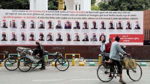 Lucknow administration put up hoardings with photographs, names, and addresses of 57 people who have been issued recovery notice for their alleged involvement in violence during anti CAA protest last December.(ANI)