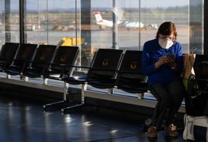 A woman with a protective face mask sits in the waiting area at Vienna International Airport in Schwechat, Austria March 16, 2020.(Reuters File Photo)