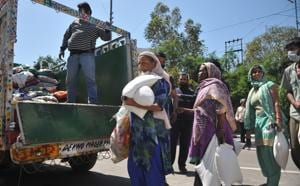 Migrant daily wage labourers receive essentials being distributed during the lockdown in Jammu on Sunday.(Nitin Kanotra)
