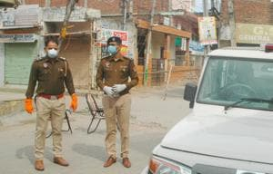 Police personnel stand guard near a sealed road in Nayagaon that leads to the house of 65-year-old man who was tested positive for Covid-19 on Monday.(Anil Dayal)
