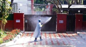 An MC worker sanitising the house of UT health secretary Arun Kumar Gupta whose daughter is under home quarantine in Sector 16, Chandigarh, on Sunday.(anil dayal/ht)