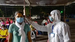 A medic checks the temperature of a student from Kota upon her arrival in Indore last week.(PTI Photo)