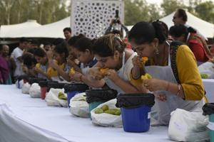 Messy magic: A mango-eating competition during the Mango Festival at Dilli Haat in New Delhi in June 2018.(Burhaan Kinu/ Hindustan Times)