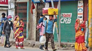 Migrant workers carrying their luggage walk towards their villages in Guwahati on Tuesday.(PTI)
