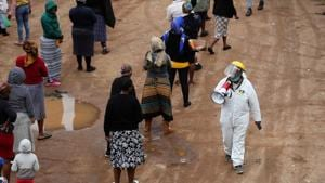 A man in protective clothing speaks trough a loudspeaker as he addresses locals queueing ahead of food distribution amid the spread of the coronavirus disease, in South Africa on April 28.(Reuters Photo)