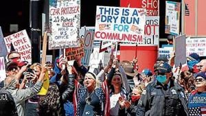 Angry protesters hold banners during a demonstration demanding the reopening of the US economy, in Chicago, Illinois.