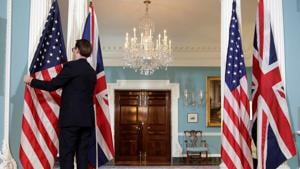 A State Department employee adjusts flags before a cancelled bi-lateral photo between US Secretary of State Rex Tillerson and British Foreign Minister Boris Johnson at the State Department in Washington, US March 22, 2017.(REUTERS)